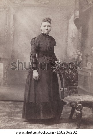 USA - WISCONSIN - CIRCA 1890 - A vintage Cabinet Card  photo of a young woman standing. The woman is dressed in a Victorian style dress. A photo from the Victorian era. CIRCA 1890 - stock photo