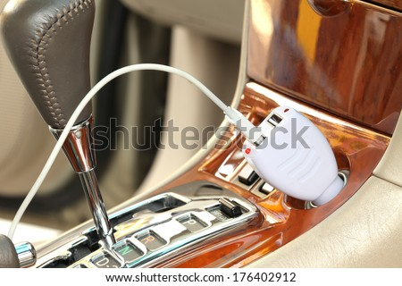 USB adapter converter plug with charging cable on a car - stock photo