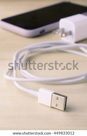 USB connector, USB cable charger for smartphone on wooden background.