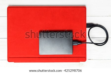 USB External hard disk on Red tablet computer - stock photo