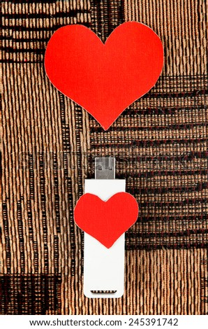 USB Flash Drive with Heart Shape on the Fabric Background - stock photo
