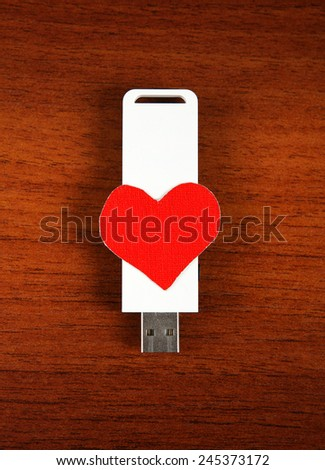 USB Flash Drive with Heart Shape on the Wooden Background - stock photo