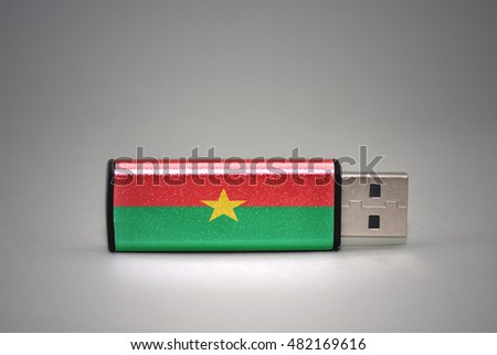 usb flash drive with the national flag of burkina faso on gray background. concept