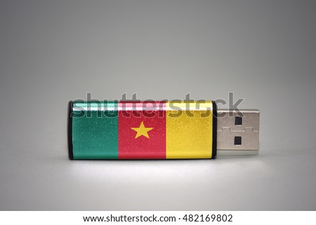 usb flash drive with the national flag of cameroon on gray background. concept