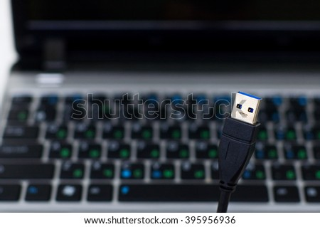 "USB 3.0 plug ""looking"" and ""grinning"" at camera, with black laptop keyboard in background  - stock photo"