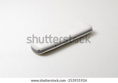USB portable modem. Used to connect internet by using simcard. Shoot over white background. Shallow depth of field. Focus on the closes distance. - stock photo