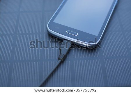 Use of renewable energy - Mobile Phone Chargers on grass in nature with Sun