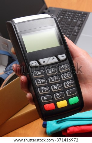 Use payment terminal for paying for purchases in store, enter personal identification number, credit card reader, clothes and laptop, finance concept