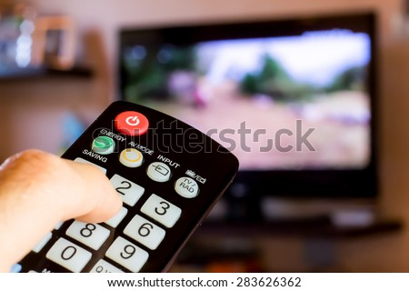 use the remote control to change channels on Television - stock photo