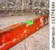 Used and dirty spirit level above a rough unfinished concrete wall - stock photo