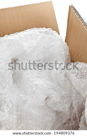 Used bubble wrap plastic in brown carton box - packaging or moving concept - stock photo