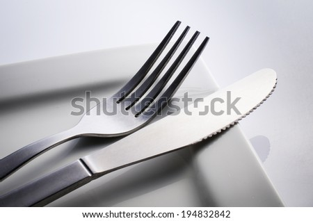 Used Cutlery set with Fork, Knife on white dish, isolated on gray background .  - stock photo