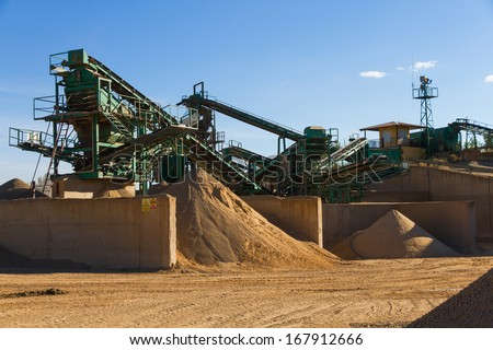 Used gravel pit near the river to mills, conveyor belts and piles of sand