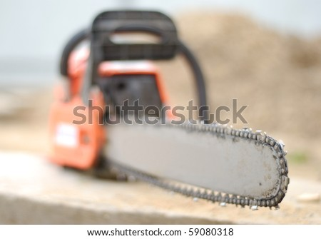 Used manual red chain saw. Focus on the verge of blade. - stock photo