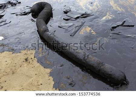 Used Oil Containment Boom on the sand beach that covered with Crude Oil on oil spill accident on Ao Prao Beach at Samet island on July 2013 in Rayong province, Thailand. - stock photo