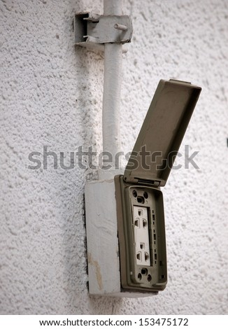used old dirty outdoor electric socket with rain cover mounted on a wall with open cover