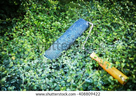 Used Paint roller lay on green plant background - Environment concept background