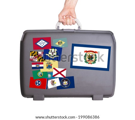 Used plastic suitcase with stains and scratches, stickers of US States, West Virginia - stock photo