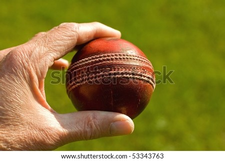 Used red leather cricket ball being held by hand against a green grass background - stock photo