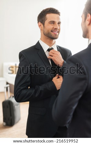 Used to look perfect. Handsome young man in formalwear adjusting his necktie and smiling while standing against mirror in hotel room - stock photo