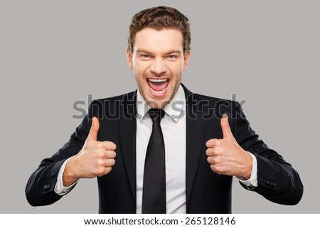 Used to success. Cheerful young man in formalwear showing his thumbs up and smiling while standing against grey background - stock photo