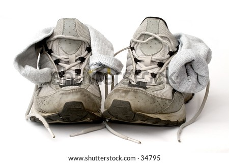 Used trainers with socks on white background. - stock photo