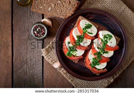Useful dietary sandwiches with mozzarella, tomatoes and rye bread. Top view - stock photo