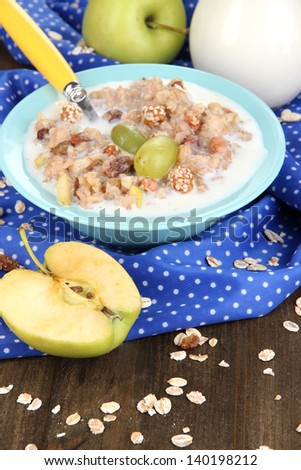 Useful oatmeal in bowl with fruit on wooden table close-up