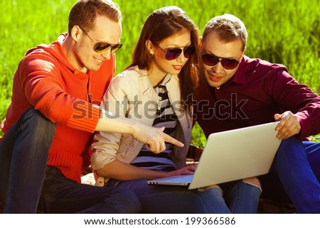 Useful weekend concept. Three happy friends having fun in the autumn park, sitting together and using laptop. Trendy casual clothing and stylish eyewear. Shiny weather. Outdoor shot - stock photo