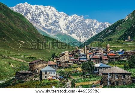 Ushguli, Georgia - July 24, 2015. View of Mount Shkhara and buildings in Ushguli community villages in Svaneti region - stock photo