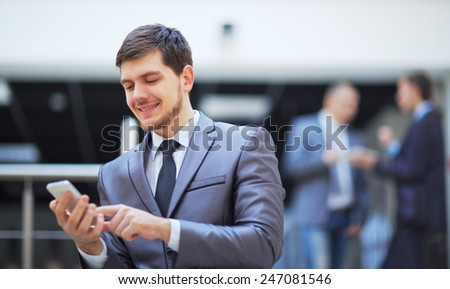 usinessman standing inside modern office building looking on a mobile phone - stock photo