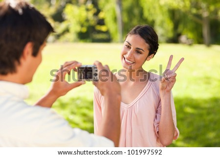 Using a camera, the man takes a photo of his friend smiling while giving the peace sign in a park - stock photo
