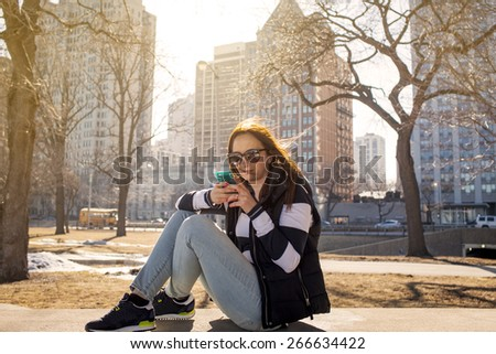 Using a smartphone outdoors - stock photo