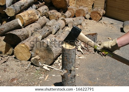 using an ax to split firewood - stock photo