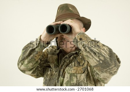 Using binoculars to look for game the hunter is checking out the area safely - stock photo