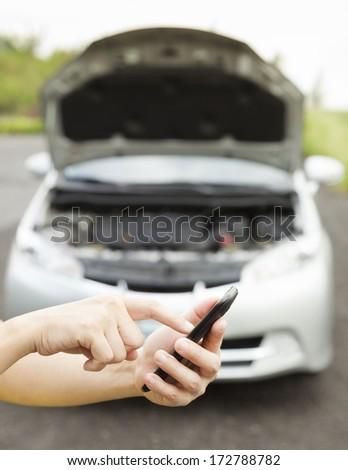 using cell phone to dial service number , a broken car - stock photo