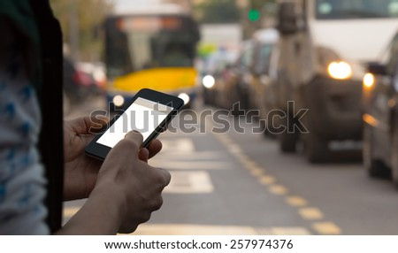 Using cellphone outdoors while waiting for the bus. - stock photo