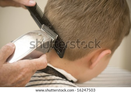 Using clippers on young boy's hair cut - stock photo