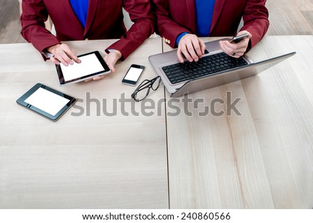 Using different digital gadgets with empty white screens on the table - stock photo