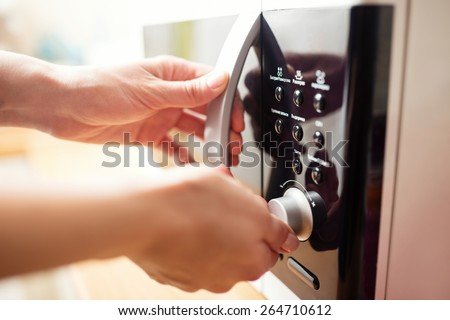 Using microwave oven, close up photo, shallow dof - stock photo