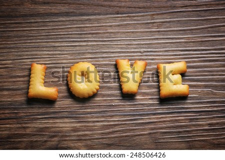 using mobile phone to take photos of Cookies ABC in the form of word LOVE alphabet with sunbeams and lens flare on old wood background, Valentines day - stock photo