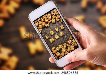 using mobile phones to take photos of Cookies ABC in the form of word LOVE MOM alphabet on old wood background, Valentines day - stock photo
