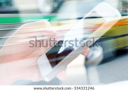 Using smart phone double exposure and blurred view of car on city street  - stock photo