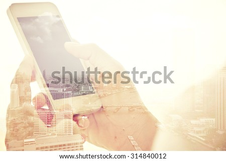 Using smart phone double exposure and cityscape background. Business & technology concept.  - stock photo