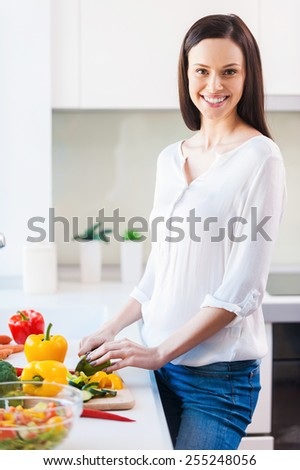 Using the freshest veggies for my meal. Beautiful young woman cutting vegetables and smiling while standing in the kitchen  - stock photo
