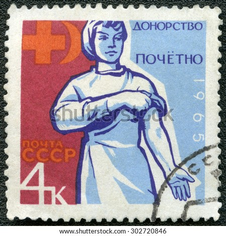 USSR - CIRCA 1965: A stamp printed in USSR dedicated Honoring blood donors, show Hand holding carnation, and donors emblem, circa 1965 - stock photo