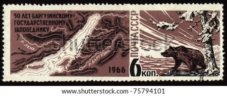 USSR - CIRCA 1966: A Stamp printed in USSR shows 50-year anniversary of Barguzinsky reserve on Baikal lake, map of Baikal region, bear on lake shore, circa 1966 - stock photo