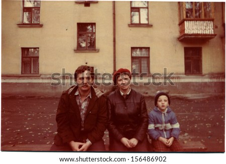 USSR - CIRCA1987: A vintage photo of young couple with son seating on the bench in the countryyard of condo, Kamensk-Shakhtinskiy, Rostov Region, Russia, USSR, 1987 - stock photo