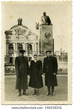 USSR - CIRCA :May 22, 1958 Vintage photo shows two men and woman on the backdrop of Lenin statue, Lviv, May 22, 1958 - stock photo