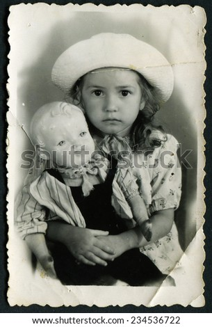 USSR - CIRCA 1980s: Portrait of little girl in a hat with a toy, circa 1980s - stock photo